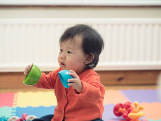 Asian baby playing toy at home