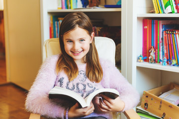 Portrait of 8-9 year old kid girl reading book at home