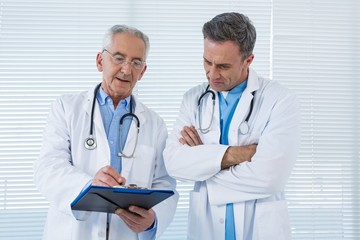 Doctors discussing over clipboard