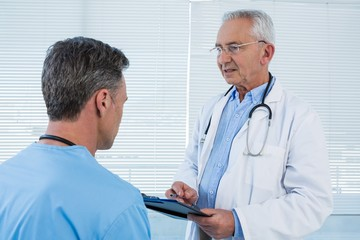 Doctor and surgeon discussing over clipboard