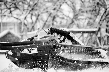 Close up of a man on a snowmobile tipping over with snow flying up for exhileration in black and white