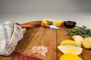 Cheese, ham and bread with various ingredients on chopping board