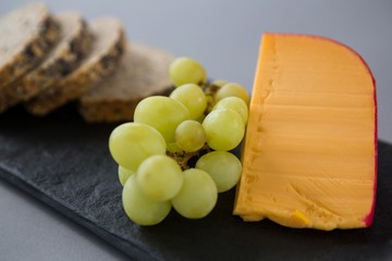 Gouda cheese and grapes on slate plate