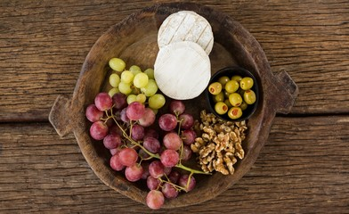 Cheese, grapes, olives and walnut on wooden serving plate