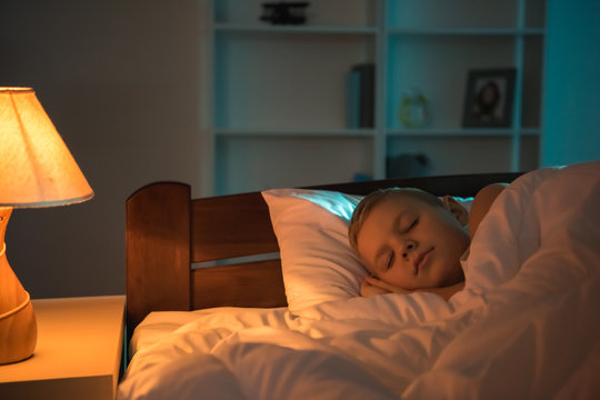 The young boy sleeping on the bed at night