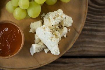 Cheese with grapes and sauce on wooden plate