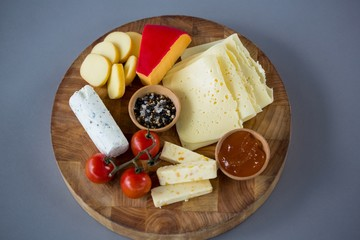 Variety of cheese with cherry tomato and spices on wooden board