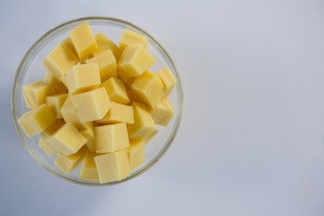 Cubes of cheese in a bowl against white background