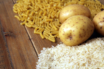 Rice, potatoes and macaroni pasta on a wooden table.Three common carbohydrates which provide energy but can cause obesity