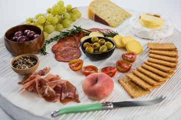 Variety of cheese with grapes, olives, salami
