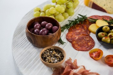Variety of cheese with grapes, olives, salami and crackers