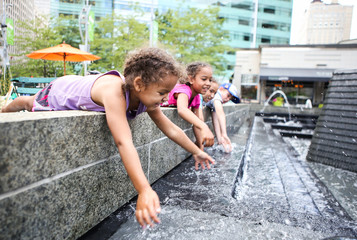 Children playing in a city fountain. Shallow focus on girls face