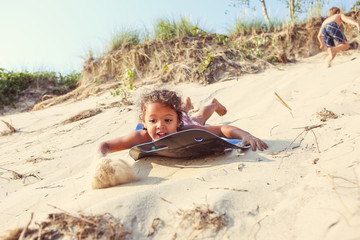Young girl sliding down a sand dune on a sled in the summer. Som