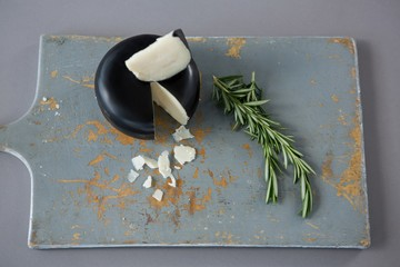 Gouda cheese with rosemary leaves on chopping board