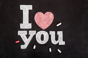 Black chalkboard with text I love you and chalks