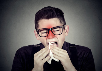 Man with cold sneezing in tissue