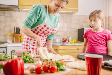 Mother and daughter preparing pizza