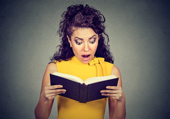 Amazed shocked woman reading a book