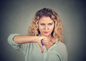 Woman giving thumb down gesture looking with negative expression
