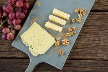Pieces of cheese, walnut and grapes on chopping board
