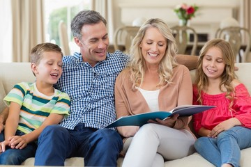 Parents and kids sitting together on sofa with photo album