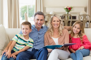 Portrait of parents and kids sitting together on sofa