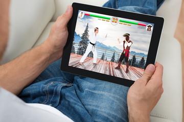 Man Playing Videogame On Digital Tablet