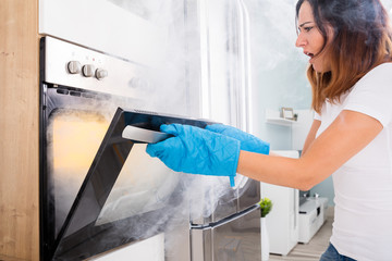 Woman Opening Door Of Oven Full Of Smoke