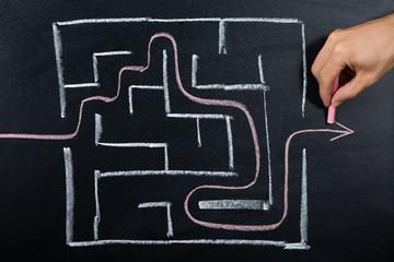 Person Solving Maze On Blackboard