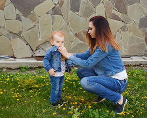 Mother and daughter in a spring park. Mother helps daughter. Girls dressed in denim jackets and jeans. Spring mood. Family time.