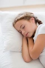 Cute girl sleeping on bed in bedroom