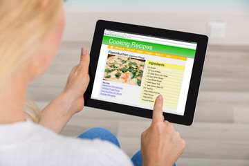 Woman Using Digital Tablet For Learning Recipe