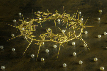 Gold crown of thorns on weathered brown grunge background with pearls scattered - Concepts of King and the Parable of the Pearl