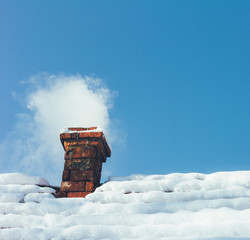 smoke out of a brick chimney on a snowy rooftop home on the background of blue sky