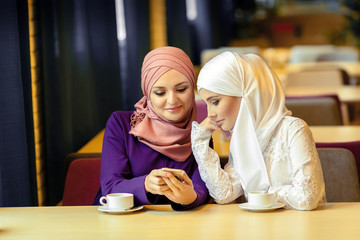 two young Muslim women sitting in a cafe and looking for something in a cell phone