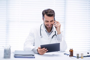 Male doctor talking on mobile phone while using digital tablet