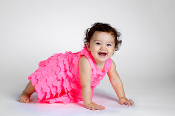 Adorable Attentive Baby Girl on all fours crawling with a huge smile on her face.