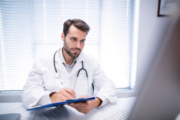 doctor writing on clipboard while working