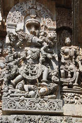 Carving on the walls of an ancient temple at Bellur in India, of Lord Ganesha, killing the rude King and crippling him below his feet