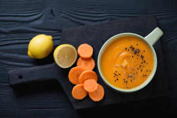 Bowl of carrot cream-soup over black wooden background, top view
