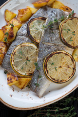 Closeup of baked seabass fillet with potato and lemon on a plate