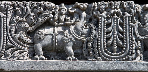 Ancient carving of a man sitting on a imaginary animal called makara