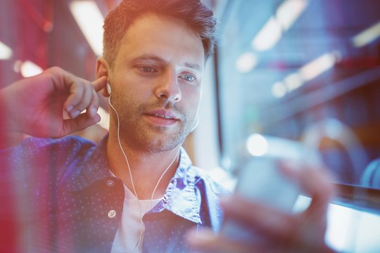 Close up of man listening music on mobile phone