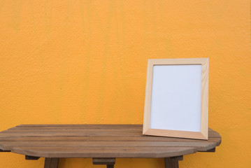 photo Frame on a wooden on Yellow background .