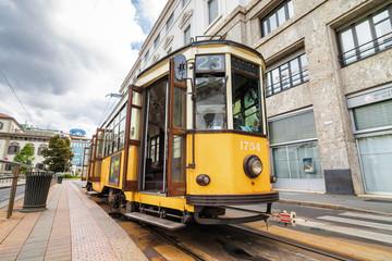 Vintage orange tram on the street of Milano near city center, Lombardia region, Italy.