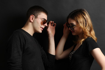 Model Girl and guy posing in stylish clothes on a black background.