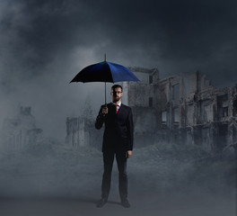 Businessman with an umbrella on city ruins