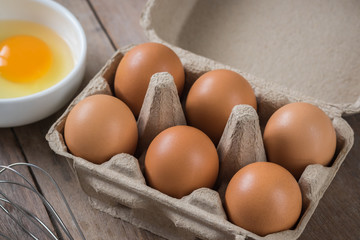Eggs in carton box and yolk in bowl