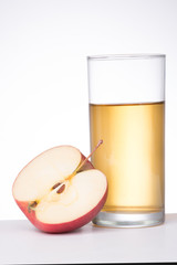 Apple with glass of juice on white background
