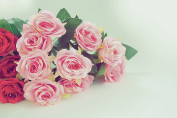 Pink and red roses bouquet on white background with copy space. Retro filter